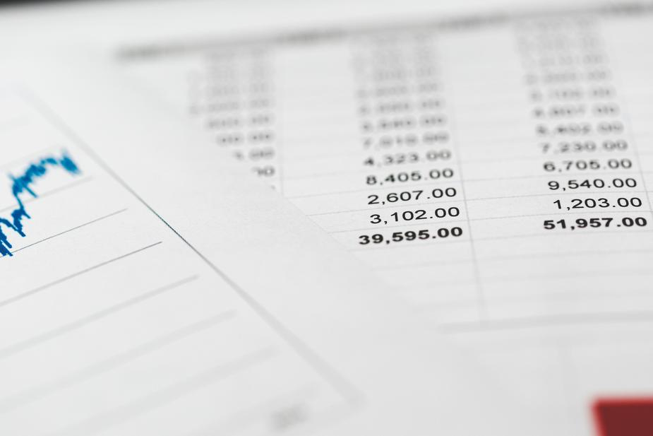A spreadsheet with financials and bills next to a chart of sales and revenue.