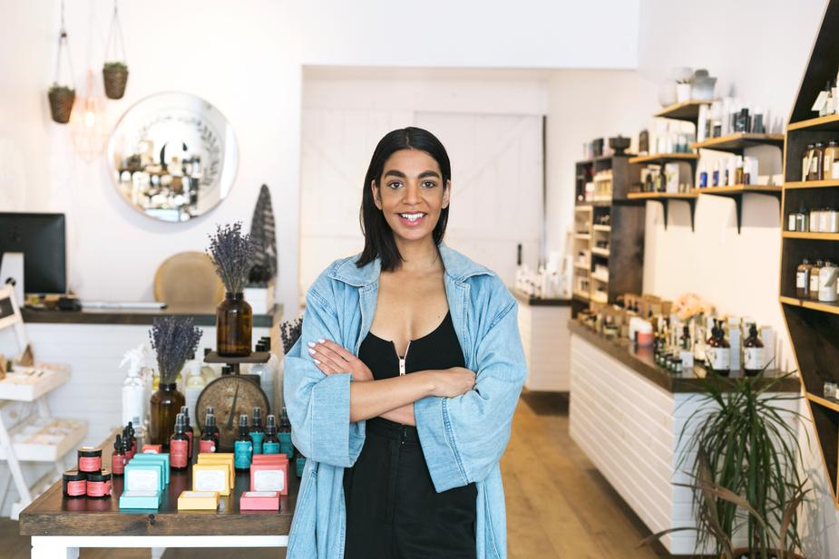 A woman business owner standing in her shop, looking proud and accomplished.