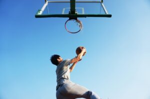 basketball player jumping to dunk the basketball in the net