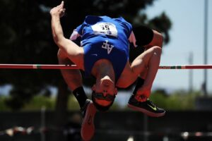 track and field runner jumping a high jump over a pole