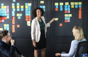 two business women and one business man setting goals for their business using post-it notes in a meeting